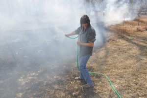Bernita Sterling, owner of a rental home at 2325 Eddy Lane in LaPorte, turns her head from the heavy smoke as she keeps the fire at bay with her garden hose. The March 15 wildfire threatened at least three homes northwest of Fort Collins. Photo by Doug Conarroe, North Forty News