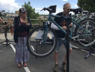 Homeward Alliance mobile bike repair. Bike owner Amy Roth looks on as volunteer Jim Smith adjusts her brakes.