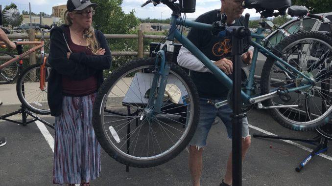 Homeward Alliance mobile bike repair. Bike owner Amy Roth looks on as volunteer Jim Smith adjusts her brakes.