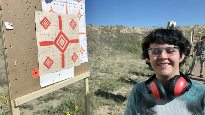 Natalie Duncan proudly poses with her target after large-bore shooting practice.